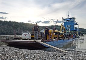 Our excavator is loaded onto a barge and goes up the Yukon to Excelsior Creek.